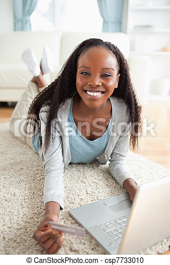 Close up of smiling woman lying on the floor with her notebook shopping online - csp7733010