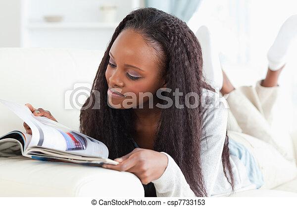 Woman looking at catalog on sofa - csp7733153