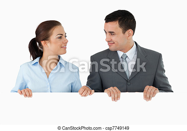 Business partners looking at each other while holding sign together against a white background - csp7749149