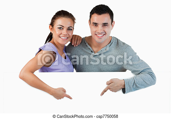 Young couple pointing at advertisement below them - csp7750058