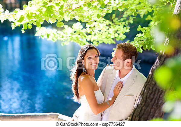 couple in love hug in forest tree blue lake outdoors