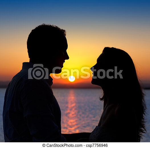 couple in love back light silhouette at lake sunset - csp7756946