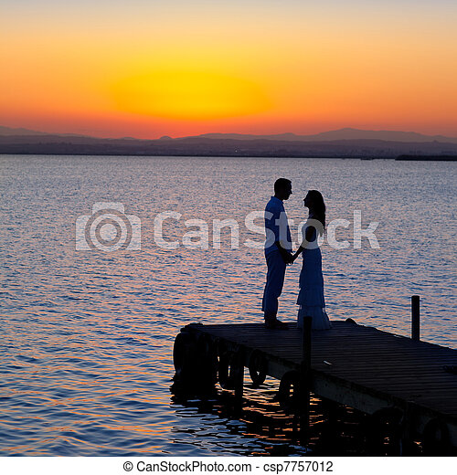 couple in love back light silhouette at lake - csp7757012