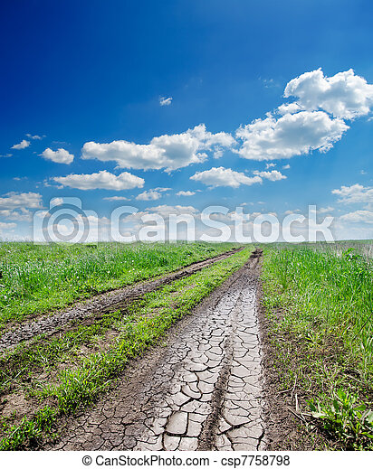 cracked rural road in green grass and cloudy sky - csp7758798