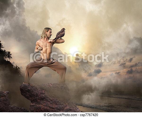 Man Practices Martial Arts with Bird of Prey at Dawn - csp7767420