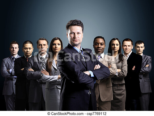 business team formed of young businessmen standing over a dark background  - csp7769112