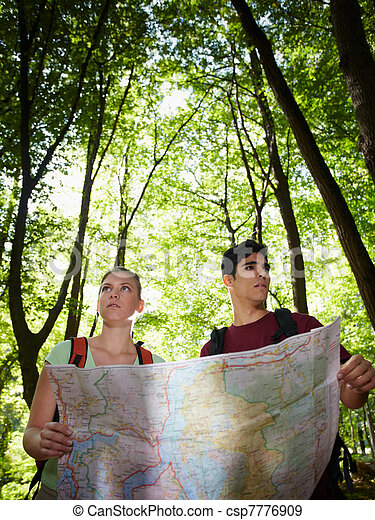 young couple looking at map during trek  - csp7776909