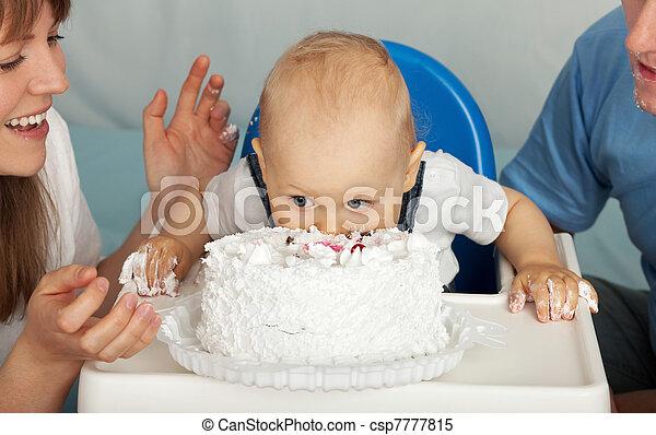 Kid eats cake. Family celebrates the first birthday of his son.