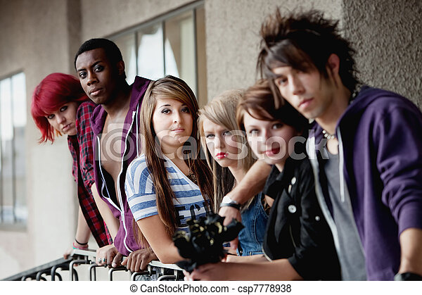 Attractive young teen punks look at the camera as it selectively focuses on the brunette in the middle. - csp7778938