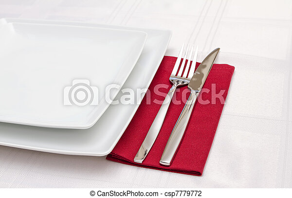 White plates with cutlery on red napkin - csp7779772