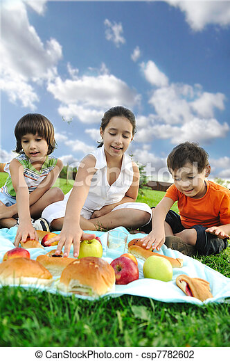 Small group of children eating together in nature, picnic, beautiful scene - csp7782602