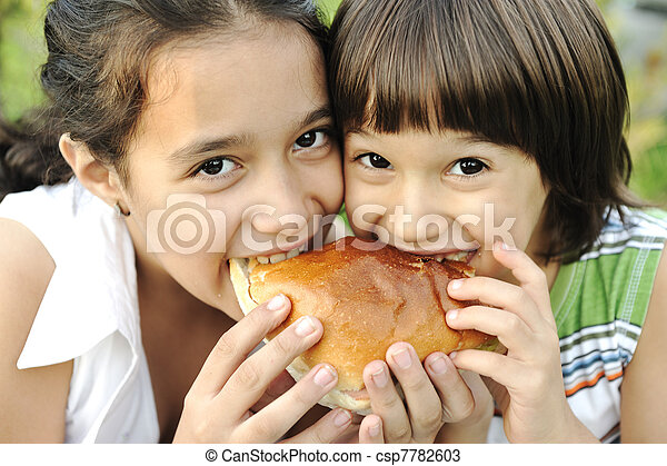 Closeup of two children eating sandwich in nature together, healthy food, careless and love - csp7782603
