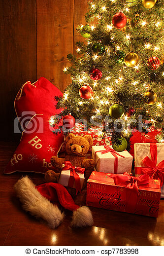 Brightly lit Christmas tree with gifts - csp7783998