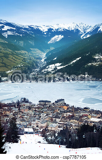 Aeral view down on Zell Am See (Austria, Alpes) town, frozen lake, ski resort and mountains in fog. - csp7787105