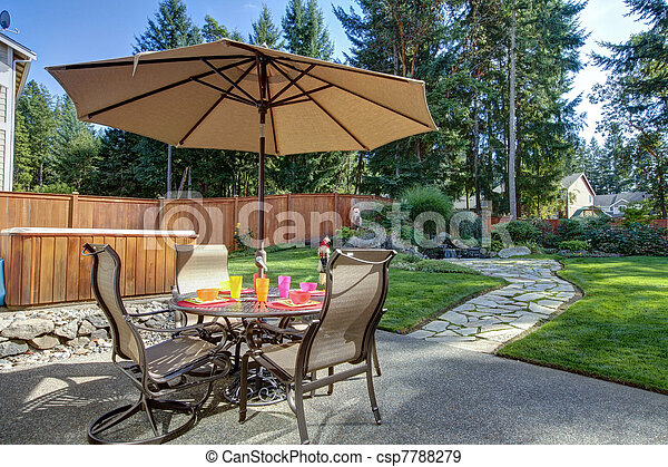 Backyard with table and unbrella - csp7788279