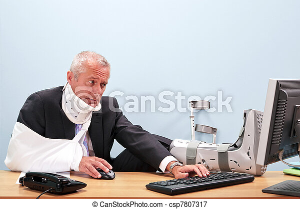 Injured businessman working at his desk - csp7807317