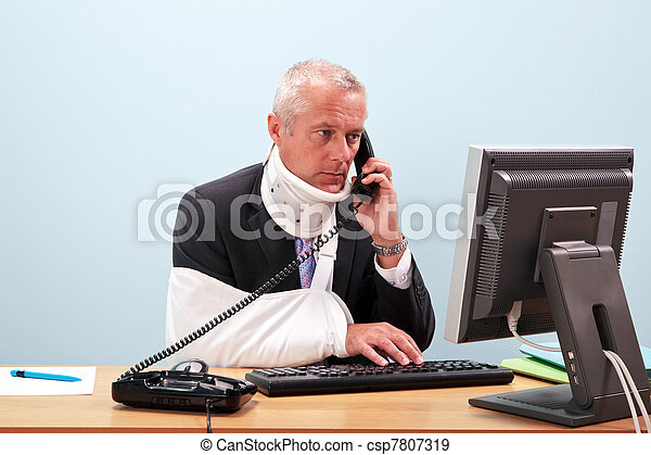 Injured businessman at his desk on the phone - csp7807319