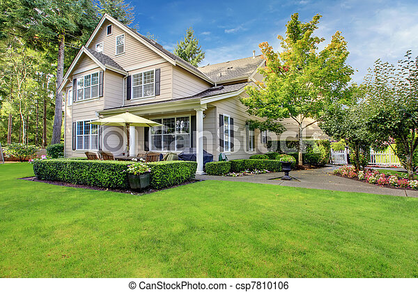 Stock image of large beige house with green grass for Jardin 5 esquinas