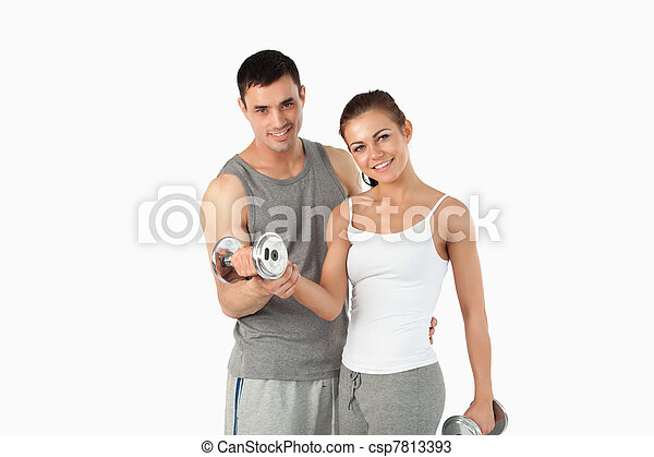 Man helping a gorgeous woman to work out - csp7813393
