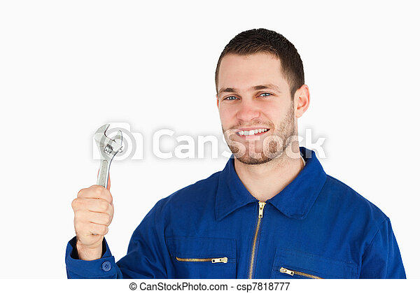 Smiling young mechanic holding his wrench - csp7818777
