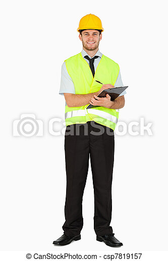 Smiling young foreman in safety jacket taking notes on his clipboard against a white background - csp7819157