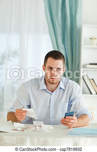 Serious looking businessman doing accounting - csp7819932