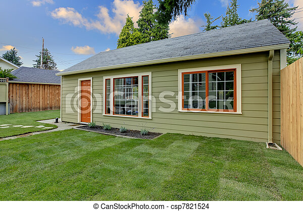 Small green guest house in the fenced backyard. - csp7821524