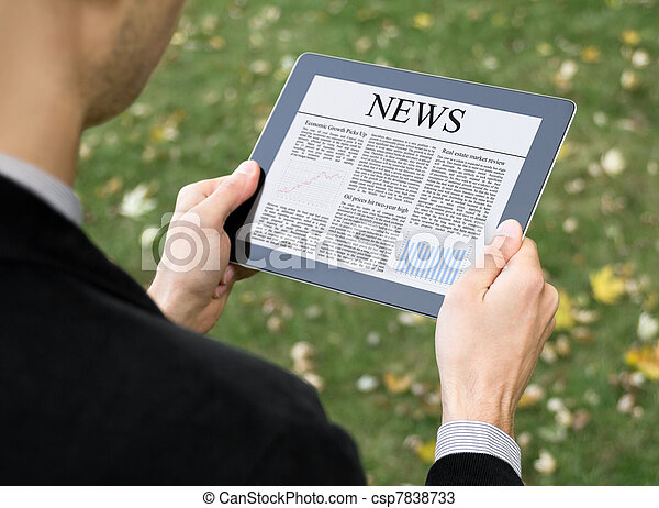 Reading News On Tablet PC - csp7838733