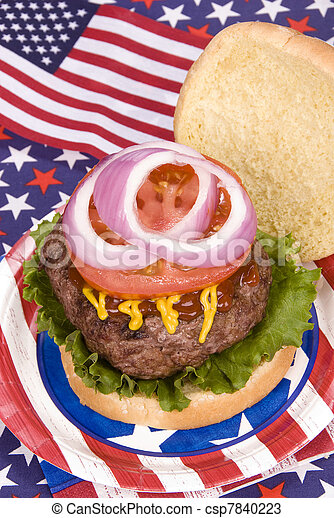 A juicy hamburger with tomoato, onion, mustard and ketchup with a fourth of July patriotic theme