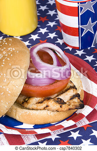 A freshly barbecued chicken burger during a fourth of July picnic.
