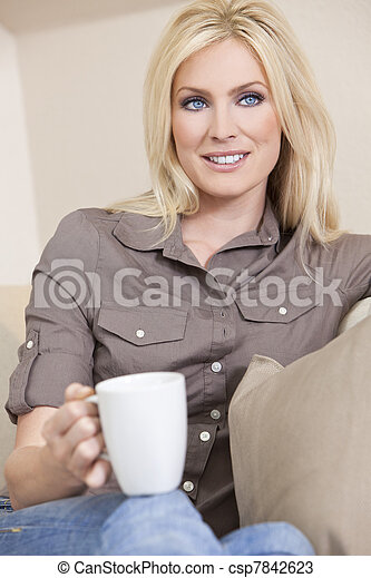 Beautiful Blond Woman Drinking Tea or Coffee At Home - csp7842623
