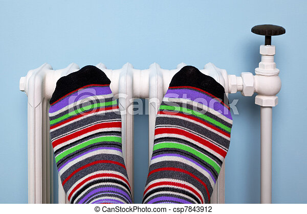 Warming feet on the radiator - csp7843912