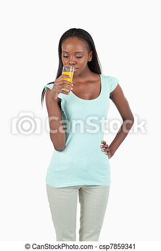Smiling young woman enjoying a sip of orange juice - csp7859341