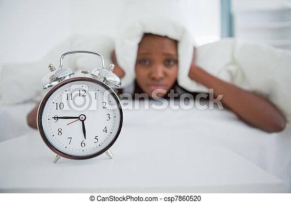 Woman being awakened by her alarm clock in her bedroom - csp7860520