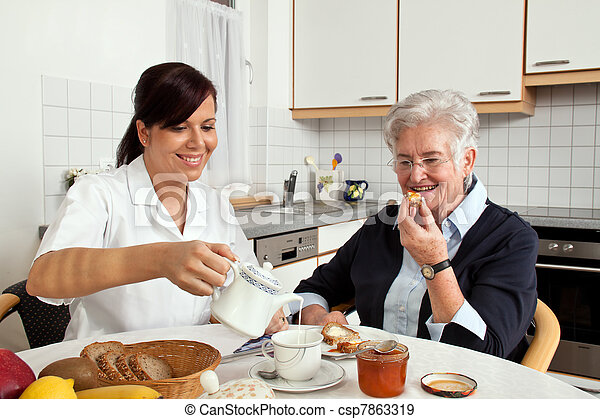 nurse helps elderly woman at breakfast - csp7863319