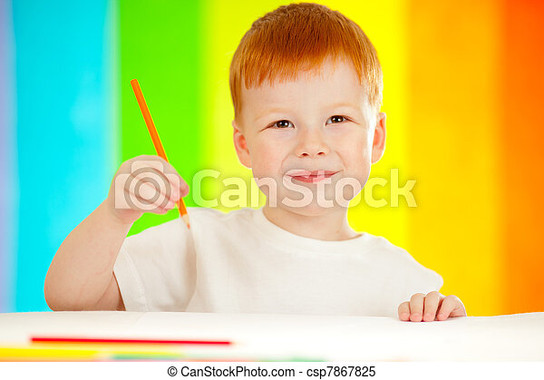 Red-haired adorable boy drawing with orange pencil on rainbow background - csp7867825
