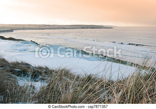 a snow covered links golf course in ireland in winter weather at sunset