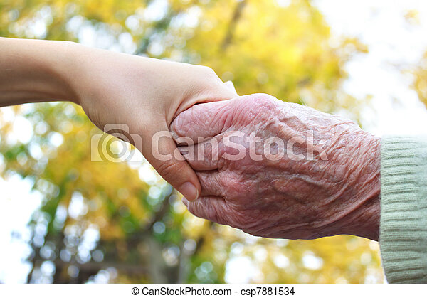 Senior and young holding hands - csp7881534