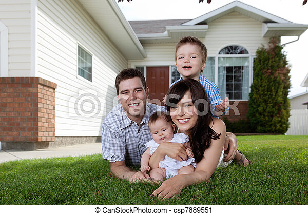 Happy Family of Four Lying Down on Grass - csp7889551