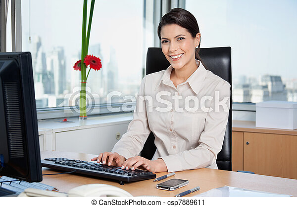 Female Entrepreneur Working On Computer - csp7889611
