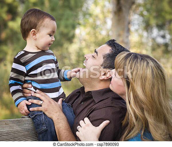 Happy Mixed Race Ethnic Family Playing In The Park - csp7890093