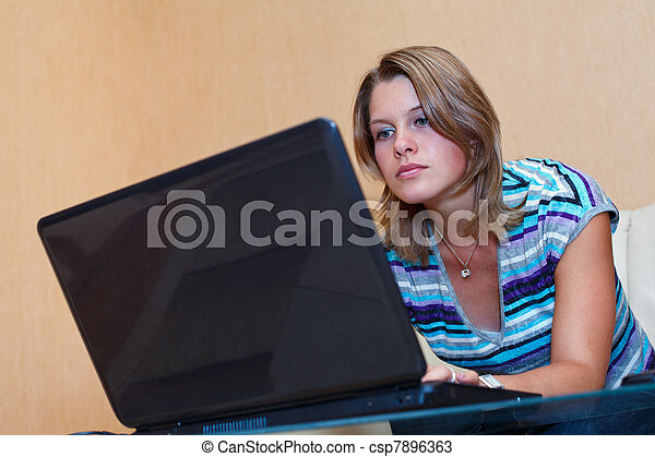 Young woman playing in games on laptop. Girl sits in domestic room interior - csp7896363