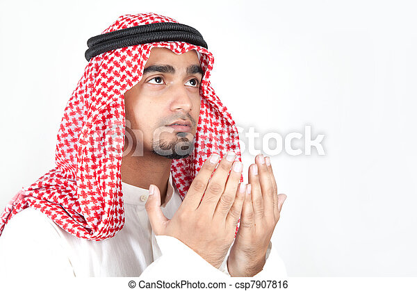 Young arab man of muslim religion praying isolated on white background - csp7907816