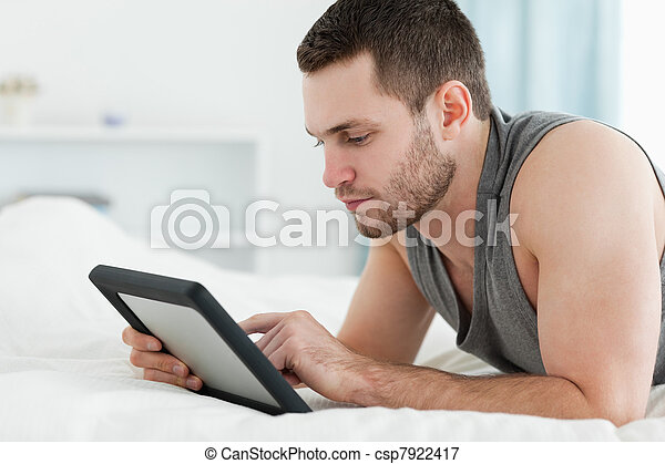 Handsome man using a tablet computer while lying on his belly - csp7922417