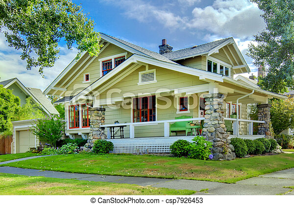 Green old craftsman style home with covered porch. - csp7926453