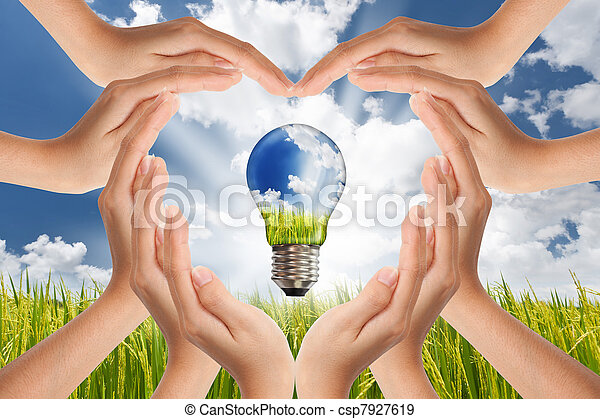 Hands saving , Global Concept of Green Energy Solutions With Light bulb and Planet on Bright Landscape - csp7927619