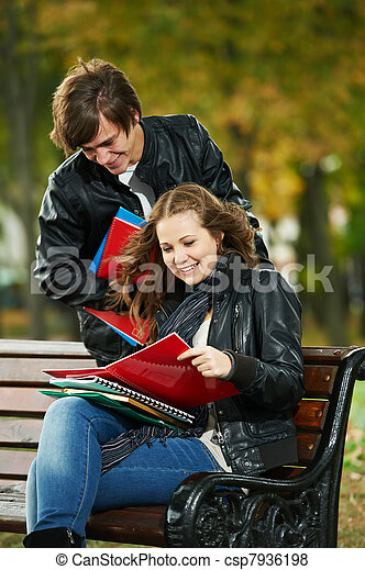 Two smiling young students studying outdoors - csp7936198