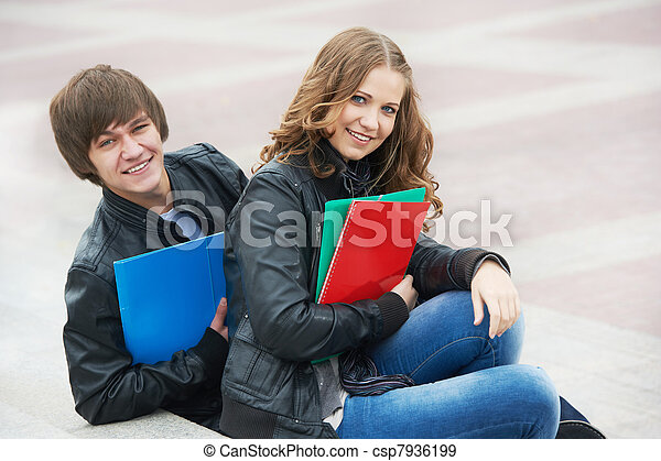 Two smiling young students studying outdoors - csp7936199