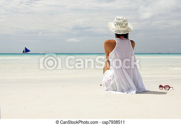 Girl in a hatn sitting on the beach and watching on the horizon - csp7938511