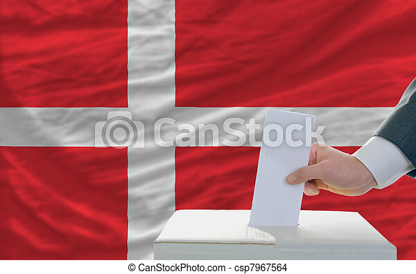 man voting on elections in denmark in front of flag - csp7967564